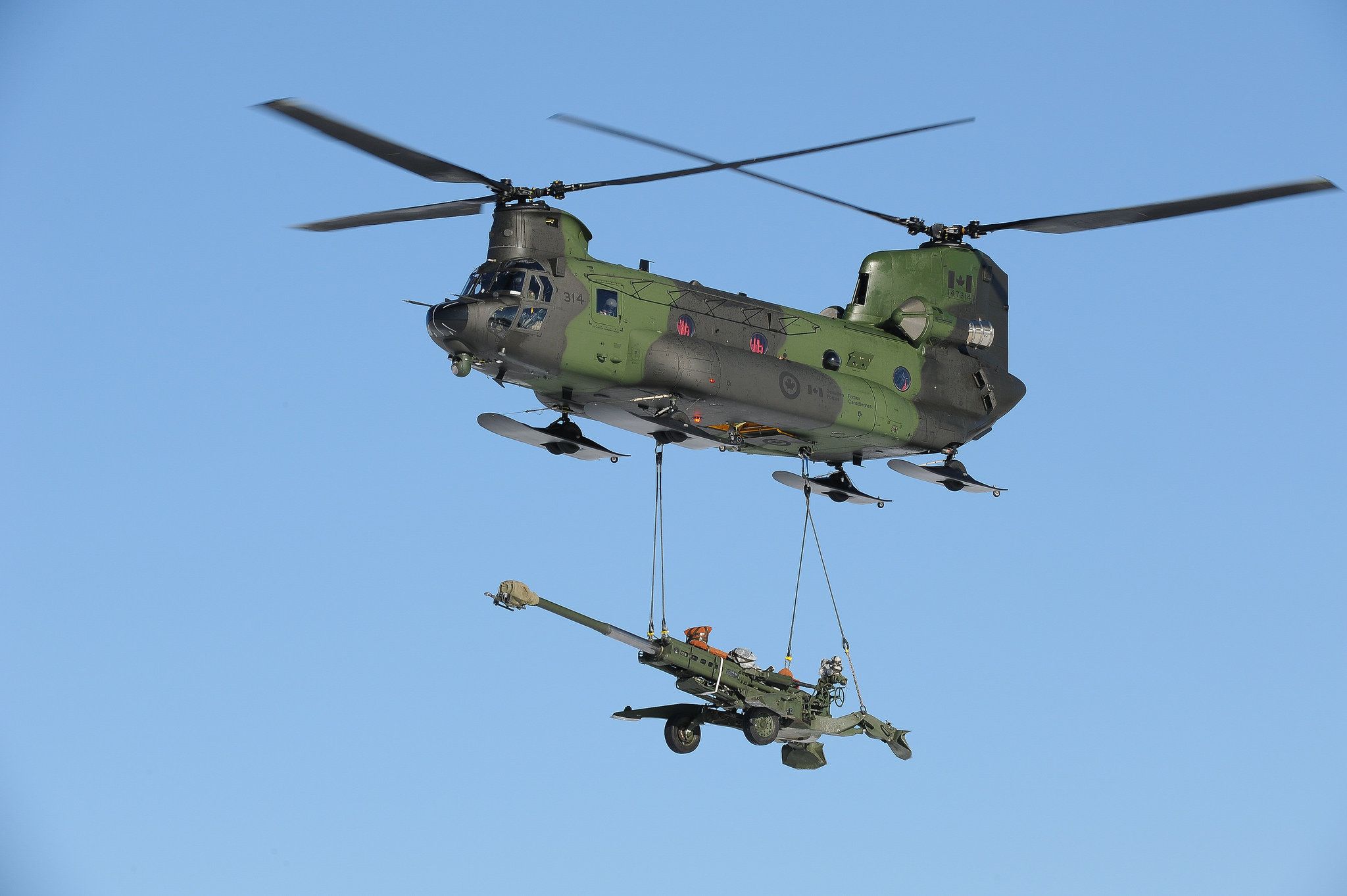A Canadian Army Helicopter carries a M777 howitzer as under sling load. Source - Net.